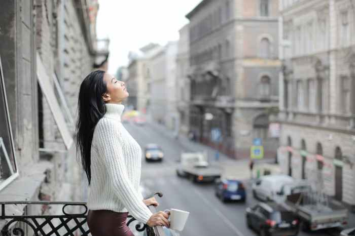 selective focus photo of woman in white sweater and maroon pants standing on a balcony with her eyes closed while holding white ceramic mug