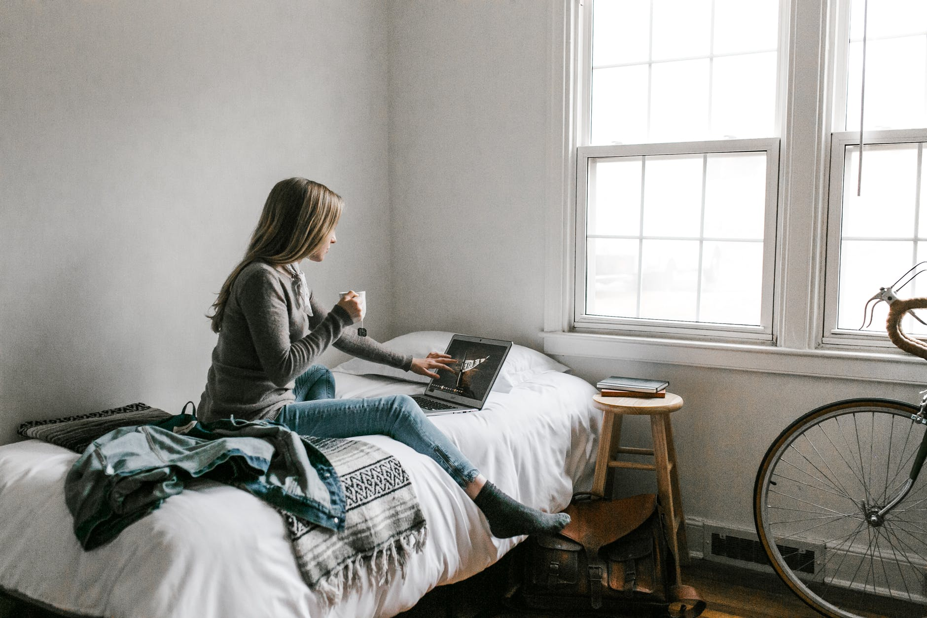 woman in gray long sleeve shirt sitting on bed reading book
